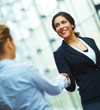 Portrait of successful young business woman shaking hands with a female colleague